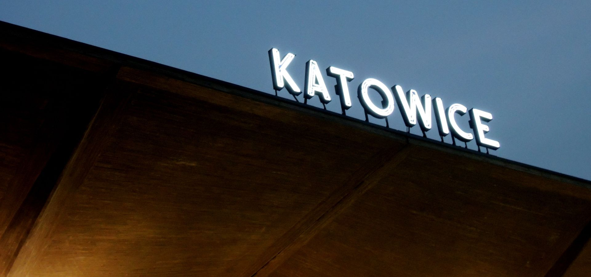 image of lettering on top of a building reading katowice, seen from below in the dark