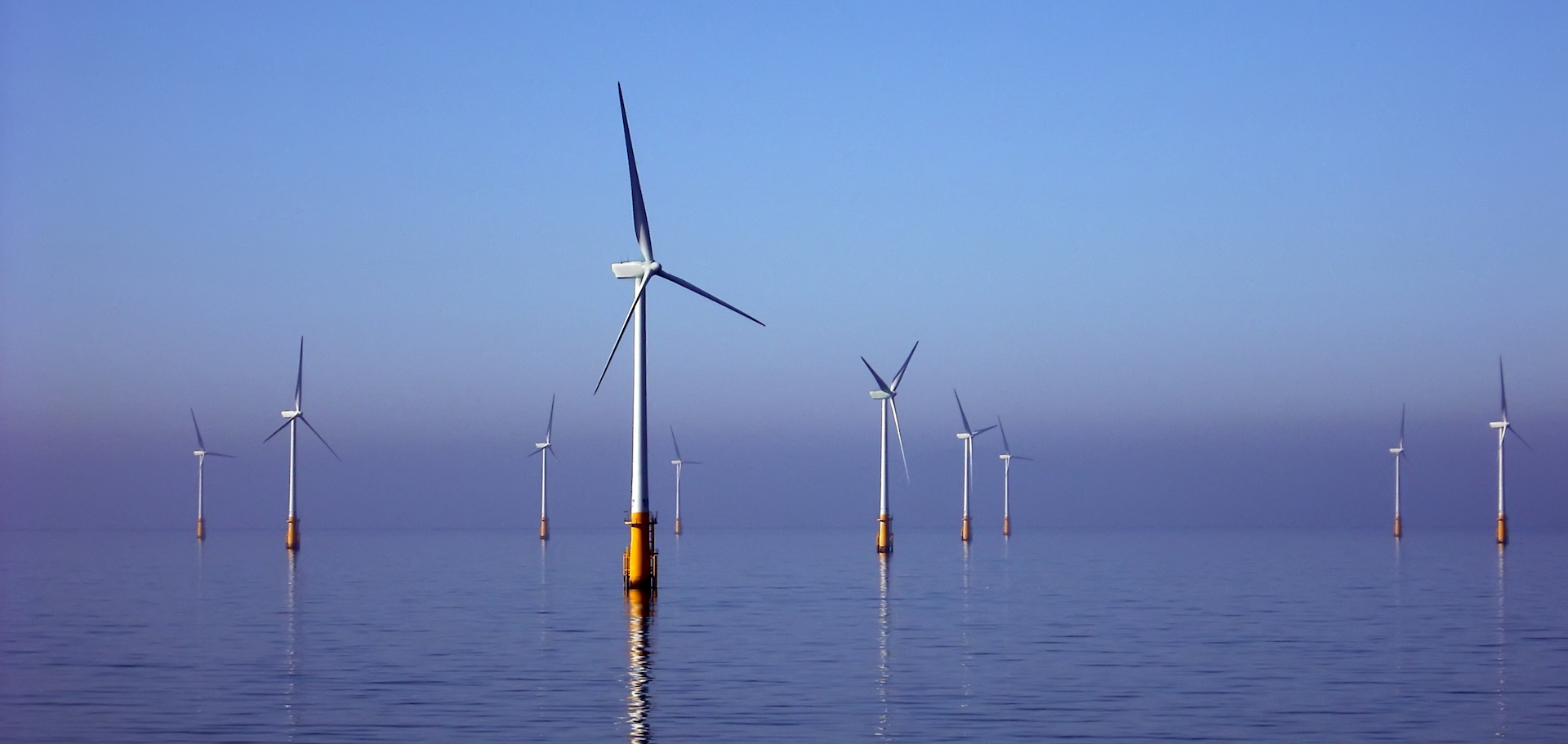view of offshore wind farm in the irish sea with turbines reflected in the water