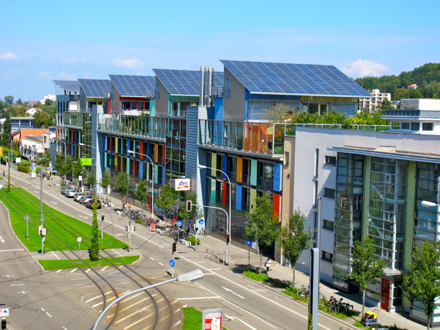 colorful apartment blocks with solar panels on top and bike lanes in front, in the residential area Solarsiedlung in Freiburg im Breisgau in Germany