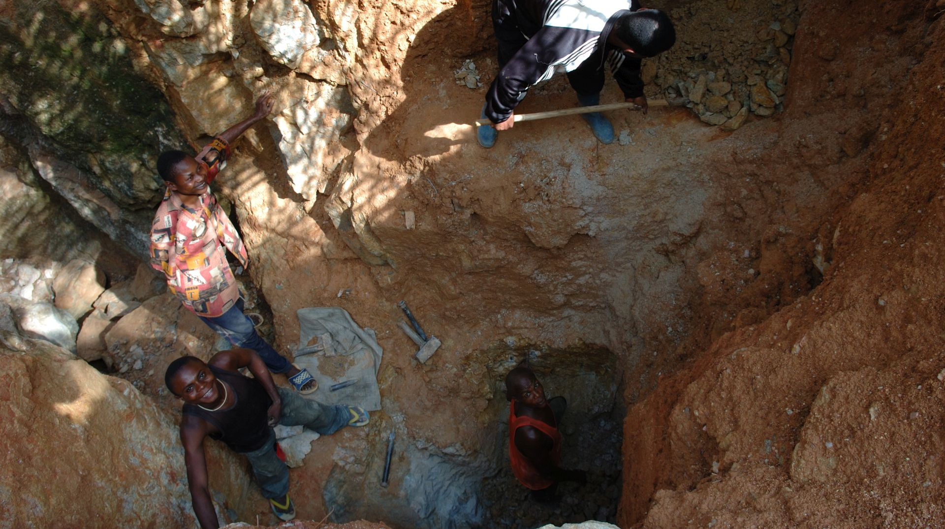 looking down into a mine with three young men working