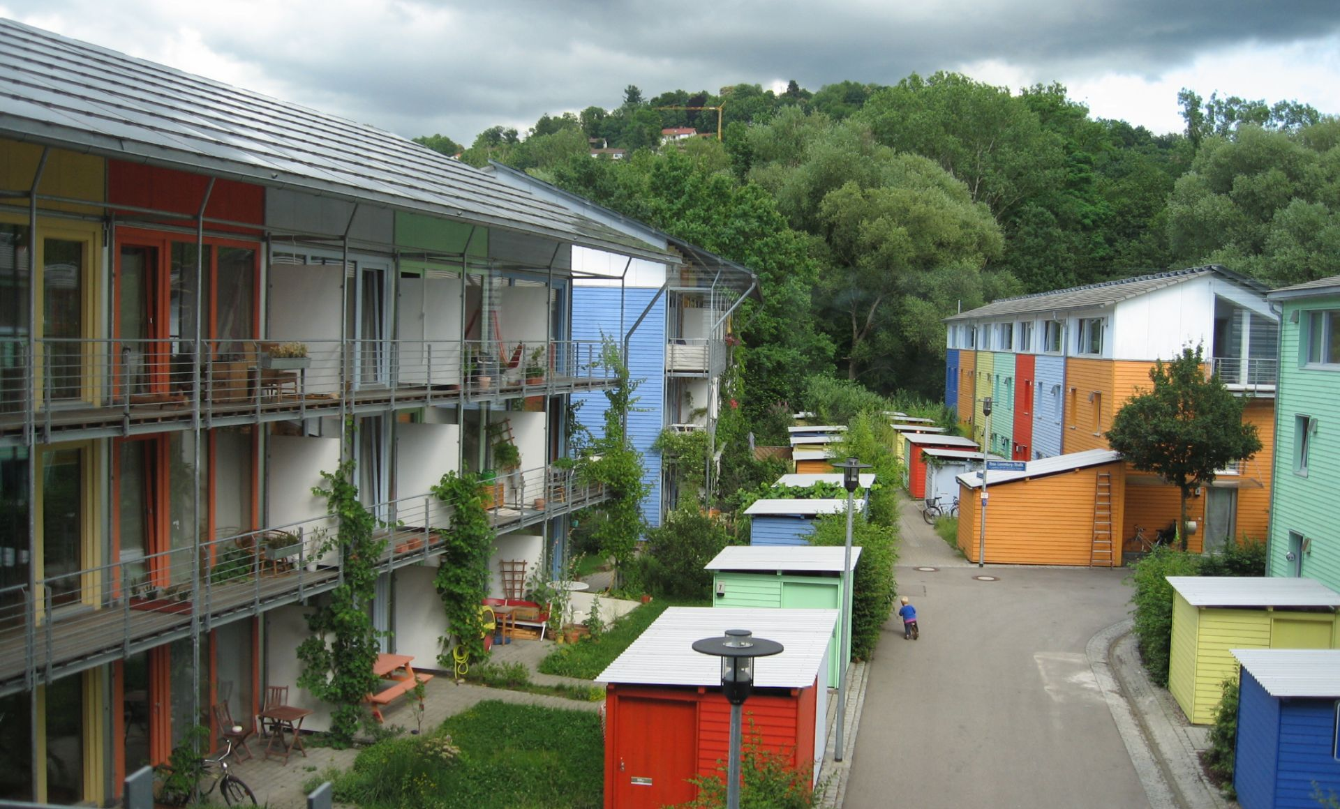 passive house homes in Freiburg with solar panels on top and child on a bike in front